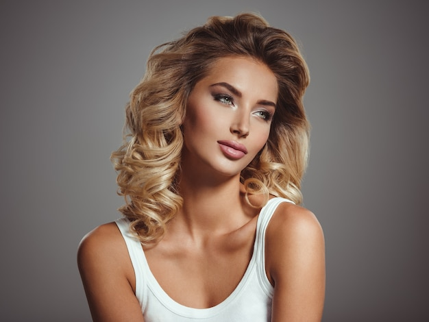 Photo of a beautiful young blond girl with curly hair. closeup attractive sensual face of white woman with long hair. smokey eye makeup.