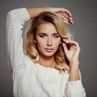 Foto di una bellissima giovane donna bionda con i capelli ricci. fronte sensuale attraente del primo piano della donna bianca. trucco occhi smokey.