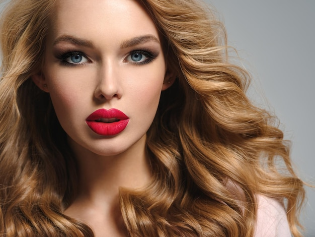 Photo of a beautiful young blond woman with sexy red lips. closeup attractive sensual face of  girl with long curly hair. smoky eye makeup