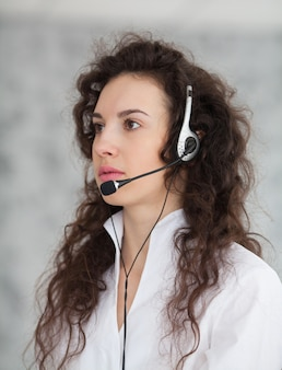 Photo of beautiful young call center operator standing over white background
