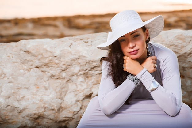 Photo of a beautiful young elegant woman in a hat by the sea
