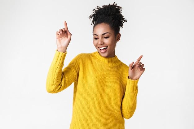 Photo of a beautiful young emotional woman posing over white wall dancing.