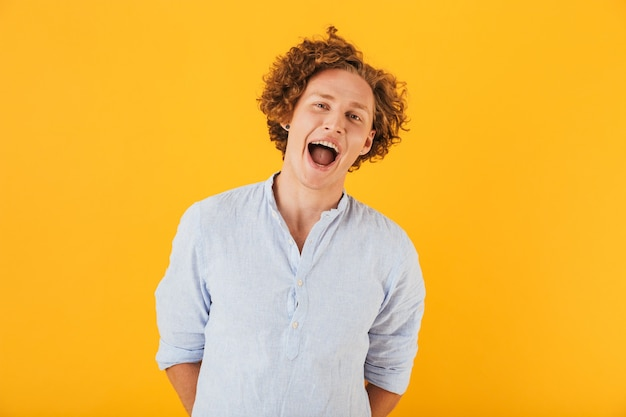 Photo of beautiful young guy  with curly hair laughing or screaming at camera with open mouth, isolated over yellow background