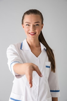 Photo of a beautiful young woman cosmetologist doctor isolated over grey wall  give you a hand for handshake.
