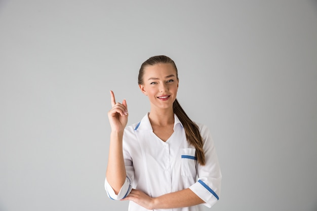 Photo of a beautiful young woman cosmetologist doctor isolated over grey wall  pointing.