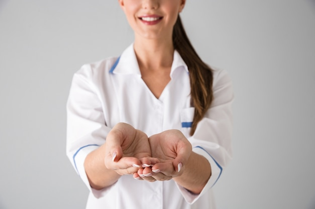 Photo of a beautiful young woman cosmetologist doctor isolated over grey wall  showing a hands.