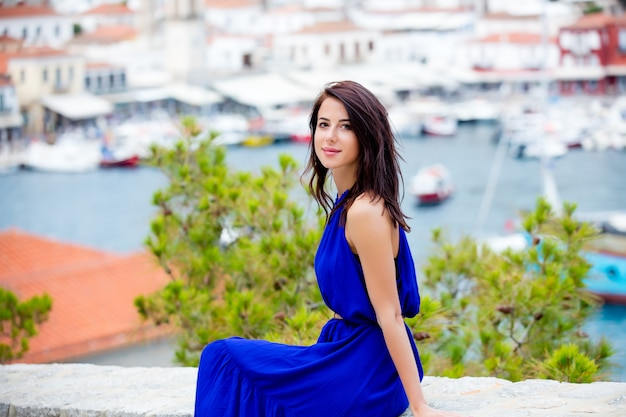 Photo of beautiful young woman sitting on the stairs on the port background in greece