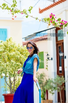 Photo of beautiful young woman standing near tree and houses in greece