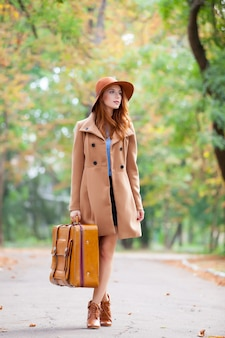 Photo of beautiful young woman with suitcase on the wonderful autumn park background