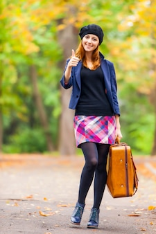 Photo of beautiful young woman with suitcase on the wonderful autumn park