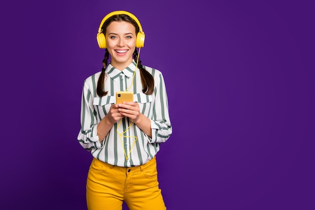 Photo of beautiful youngster lady holding telephone positive vacation time listen music wear cool earflaps striped shirt yellow trousers isolated purple color background