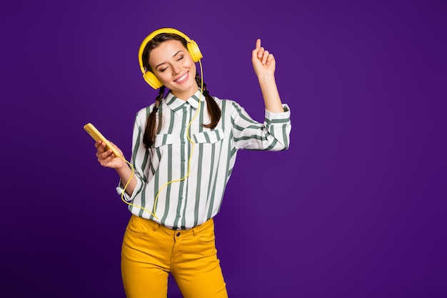 Photo of beautiful youngster lady holding telephone vacation time listen music eyes closed wear cool earflaps striped shirt yellow trousers isolated purple color background