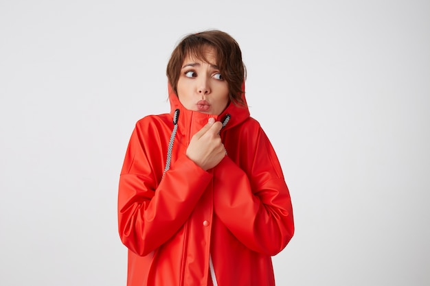 Photo of beauty young frozen and scared short haired woman in red rain coat, frowning and fearing looking up to the left, feels cold, hides in the hood. standing.