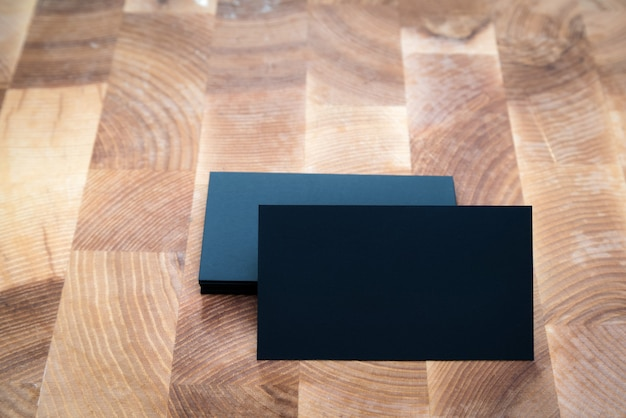 Photo of black blank business cards on wooden background.