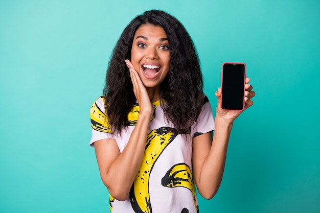 Photo of black girl hold telephone screen empty space palm cheekbone open mouth wear banana print t-shirt isolated teal color background