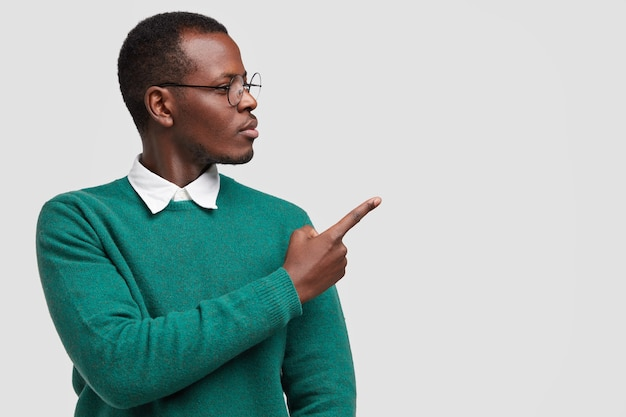 Photo of black man student demonstrates something over white copy space, points with fore finger, dressed in green sweater