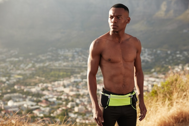 Photo of black man with pensive expression, has fitness training, poses over top view of montains, stands against copy space for your advertisement or information, being fast. motivation concept