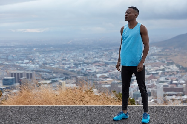 Photo of black sportsman wears blues sneakers, vest and leggings, models against altitude above horizon, big city and mountains, free space for your information. panoramic view