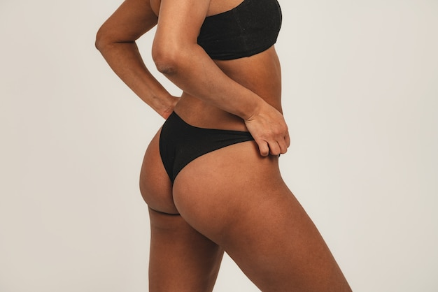 Photo of black woman wears black underwear. isolated over white background. natural beauty and health.