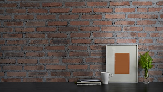 Photo of black working desk along with book, notebook, picture frame, potted plant and coffee cup putting together on it with brick wall . orderly workspace concept.