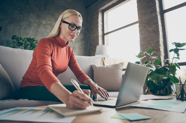 Photo of blond business lady texting notebook colleagues working home noticing startup details in organizer wear specs orange pullover sitting comfy sofa indoors