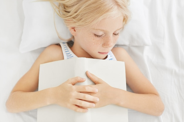 Photo of blonde little child with freckles naping in bed, keeping book in hands, feeling tiredness after long reading, falling asleep. quiet sleepy girl lying on white bed clothes with book.