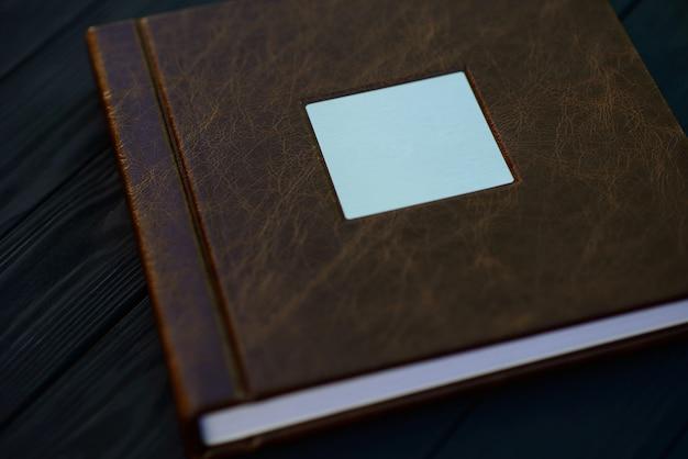本物の茶色の革で作られた写真集の表紙、黒い木製のテーブルに金属銀の銘板。