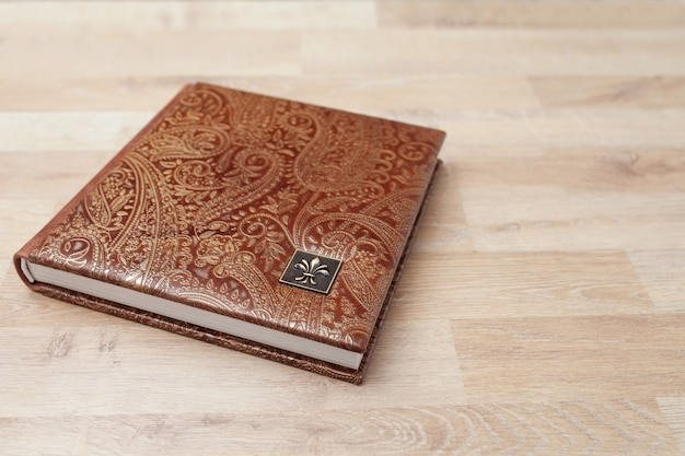 本革のカバーが付いている写真集、ノートまたは日記。茶色の装飾的なスタンピング。家族の写真アルバム。コピースペース。