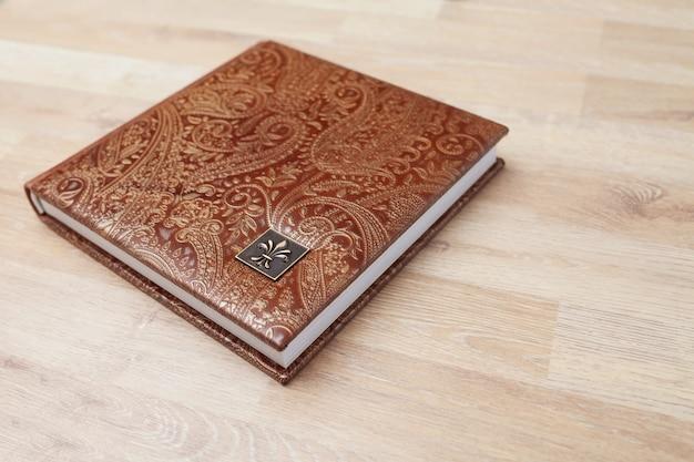 本革のカバーが付いている写真集、ノートまたは日記。装飾的なスタンピングを施した茶色の色。結婚式や家族の写真アルバム。コピースペース。