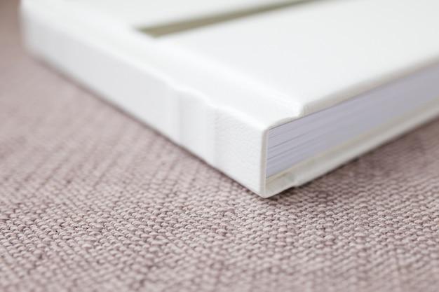 本革カバー付写真集。装飾的なスタンピングを施した白色。ソフトフォーカス。