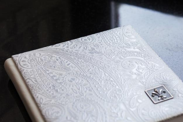 本革カバー付き写真集。装飾的なスタンピングを施した白色。結婚式や家族の写真アルバム。家族の価値