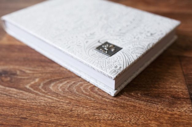 Photo book with a cover of genuine leather. white color with decorative stamping. close up picture