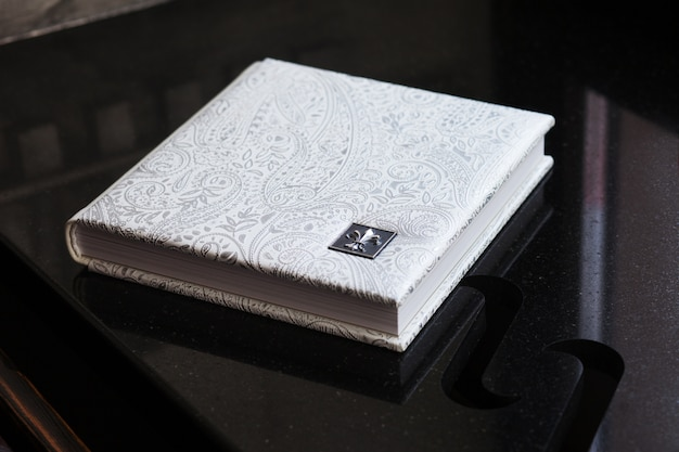 Photo book with a cover of genuine leather. white color with decorative stamping. wedding or family photo album. family value
