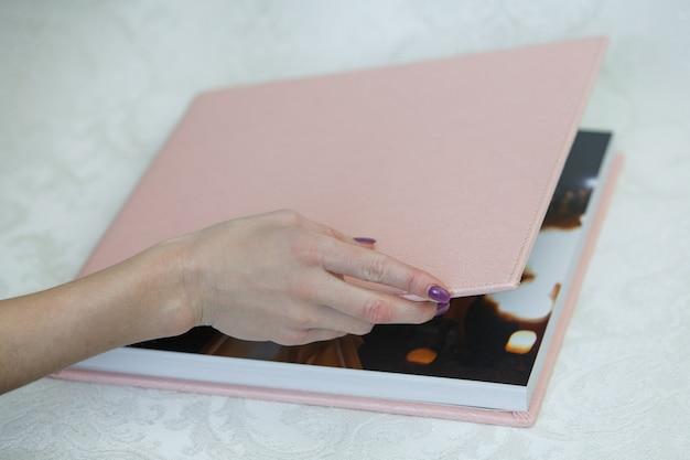 Photo book with  leather cover close up. unfolded photobook. photo book opened. sample photobook. the person is looking at a photobook.