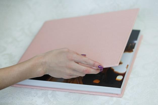 Фото книга с кожаной обложкой крупным планом. развернутая фотокнига. фотоальбом открыт. образец фотокниги. человек смотрит на фотокнигу.