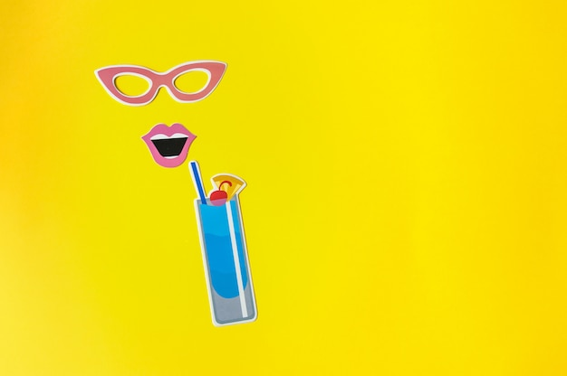 Photo booth props glasses and cocktail on yellow background