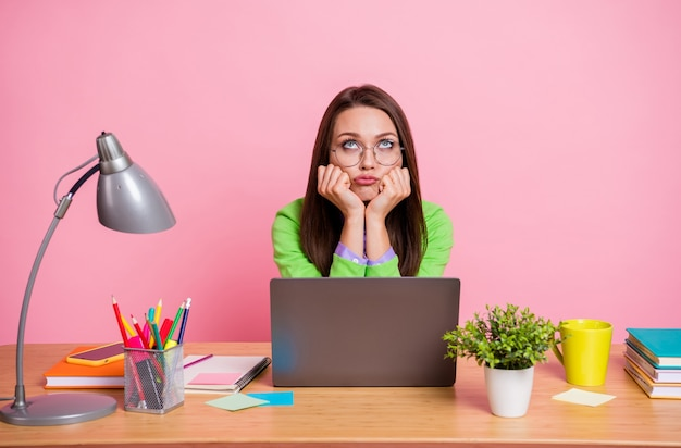 Photo of bored sad high school girl sit table work laptop wear green shirt isolated pink color background