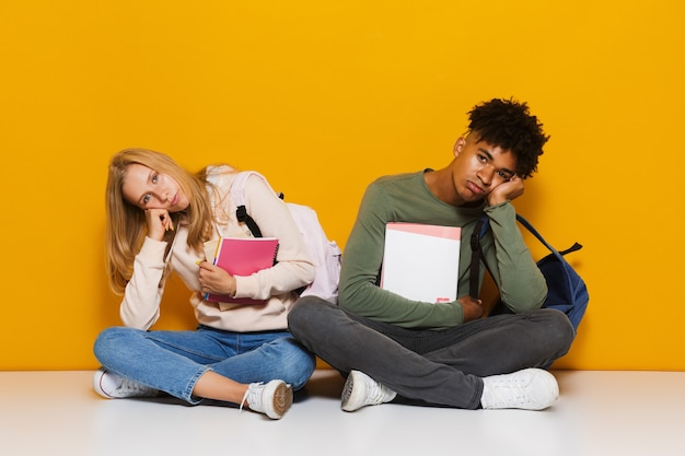 Photo of bored or upset students 16-18 using holding exercise books while sitting on floor with legs crossed, isolated over yellow background