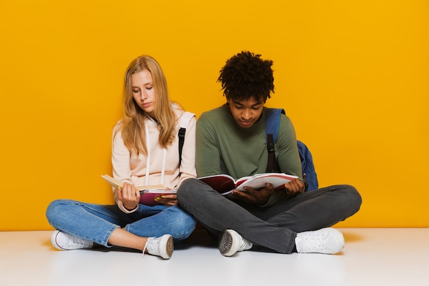 Photo of bored or upset students 16-18 using reading books while sitting on floor with legs crossed, isolated over yellow background