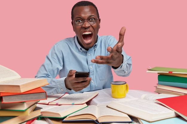 La foto di un uomo prepotente grida con rabbia e gesticola con fastidio, tiene in mano un cellulare moderno, vestito in modo formale