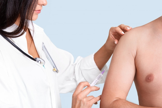 Photo of brunette female nurse in white gown with phonendoscope, makes vaccination in arm to patient