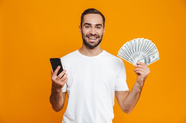 Photo of brunette man 30s in casual wear holding cell phone and fan of money, isolated