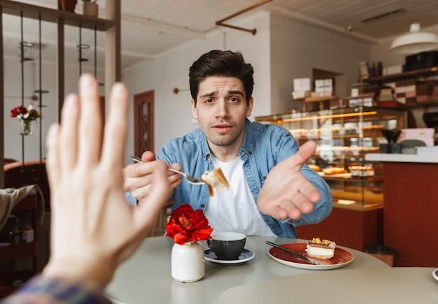 Photo of brunette man in cafe offering woman sweet cake, while woman rejecting his proposal