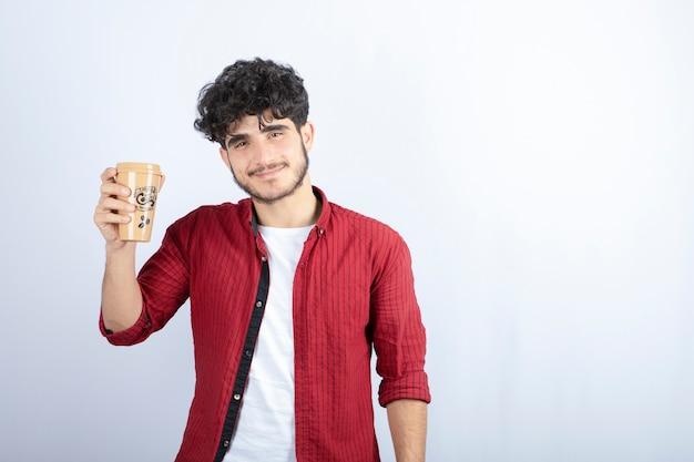 Foto dell'uomo castana che tiene tazza di caffè per tempo di pausa sopra il muro bianco.