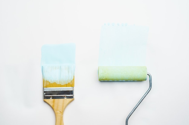 Photo of brush and roller with blue paint on blank white background