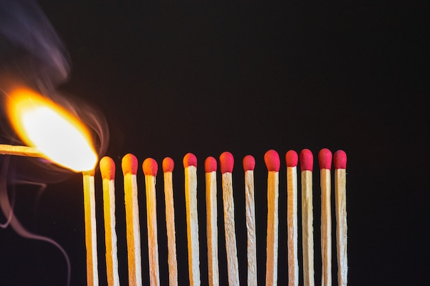 A lit match igniting a row of matches.