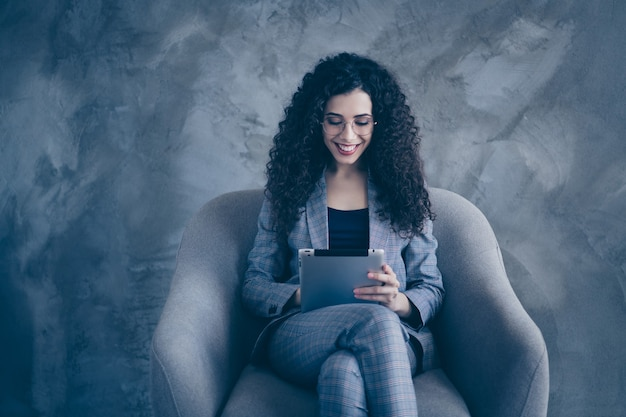 Photo of business girl sitting in chair using e-book tablet isolated over concrete wall