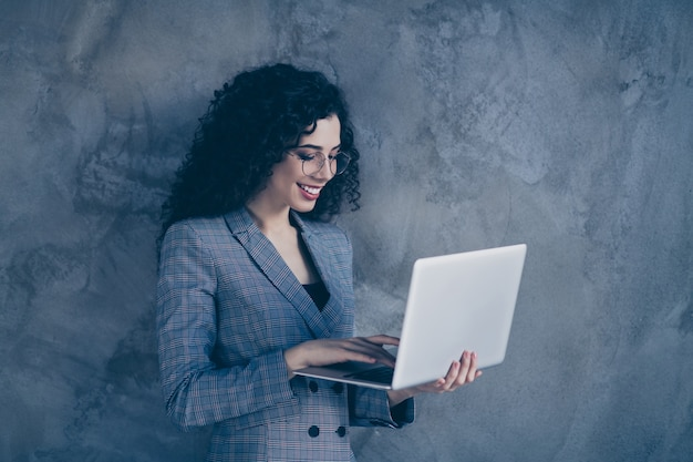 Photo of business lady using digital laptop isolated over gray wall