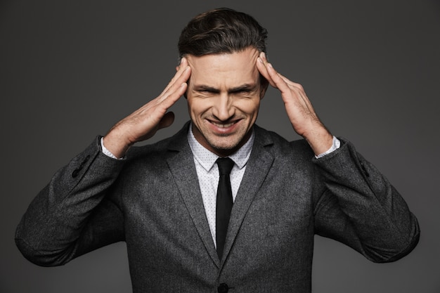 Photo of business man wearing formal suit squeezing his temples and frowning in irritation or headache, isolated over gray wall