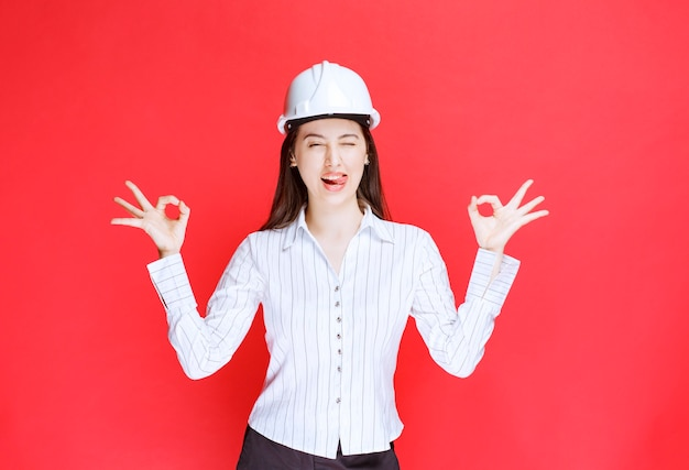Photo of a business woman in safety hat showing ok gesture .